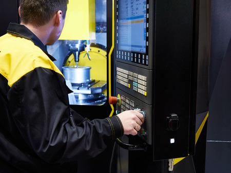 Worker controls the CNC machine