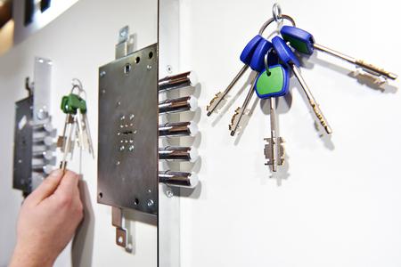 Serratura e chiavi del rivelatore del chubb della porta in deposito sulla parete bianca Archivio Fotografico
