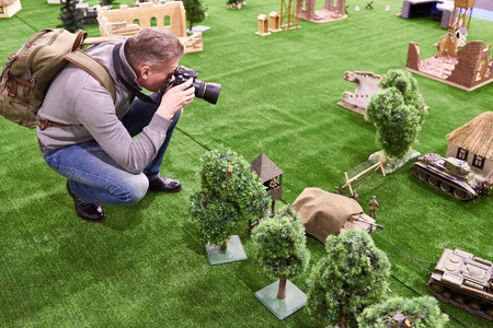 Man photographs miniatures models of military equipment and soldiers in the scene of the reconstruction of the Second World War