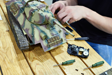 Man repairs a reduced model of soviet tank T-34 to create a miniature combat scene