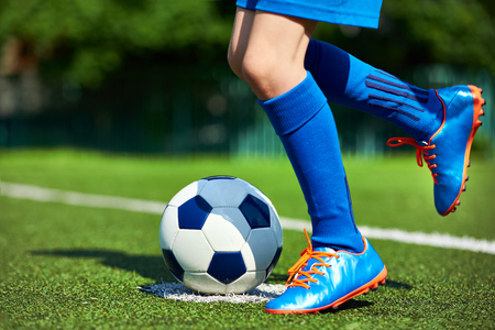 Legs of a football player boy in boots with a ball on the green lawn of the stadium Stock Photo