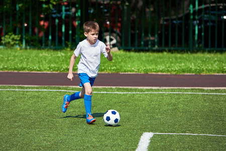 Boy football player running with a ball on the green lawn of the stadium Stock Photo