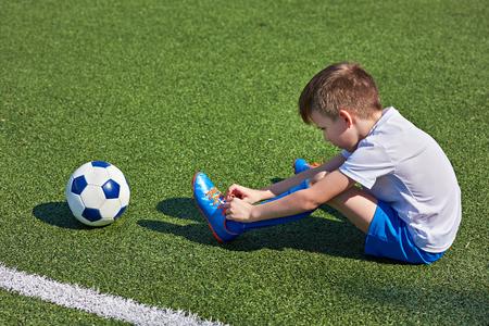 Het voetbalvoetbal dat van de jongen de veters op de laarzen op een groen gras bindt