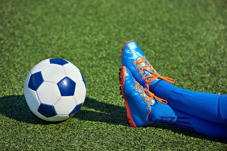 Foots of boy soccer player in football boots with ball on grass Stock Photo