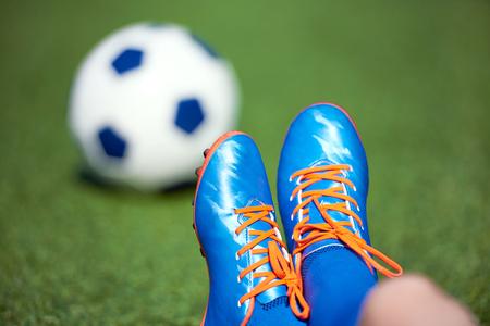 Voetbalschoenen van jongensvoetballer met bal op gras Stockfoto