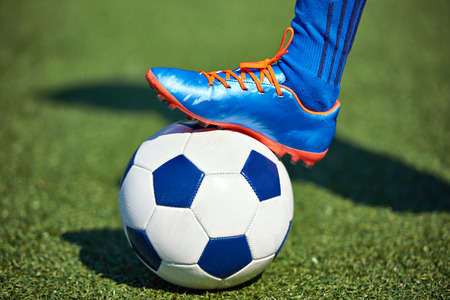 Foot of a soccer player in a football boot on a ball on an artificial green lawn of the stadium