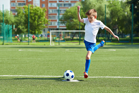 Boy soccer player with a jump before a kick on the ball