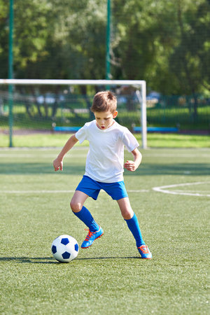 Boy soccer player running with ball on football stadium