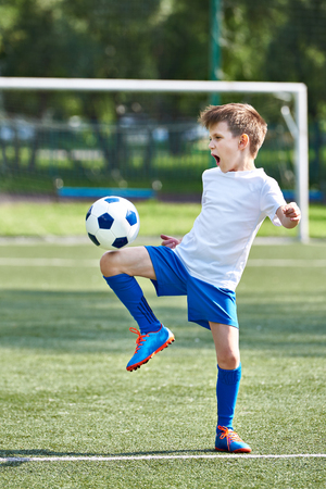 Boy soccer playing with ball on football stadium