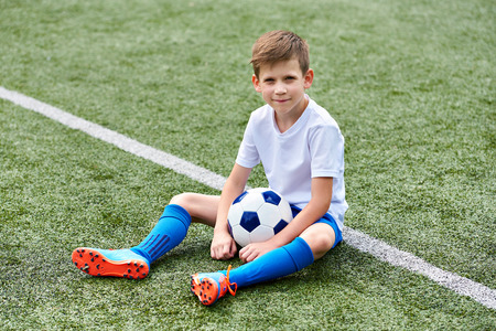 Boy football soccer with ball sitting on a green grass