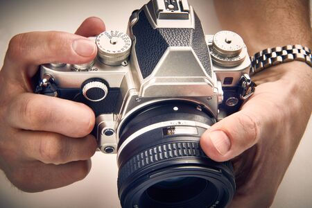 Retro SLR camera in the hands of the photographer closeup Stok Fotoğraf