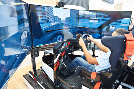 Man plays on a computer racing simulator