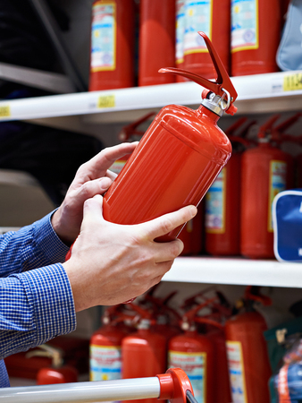 Buyer with fire extinguisher in hands at hardware store