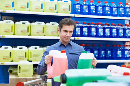 Man buys windshield washer fluid in the supermarket