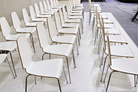 Rows of white chairs in the presentation room