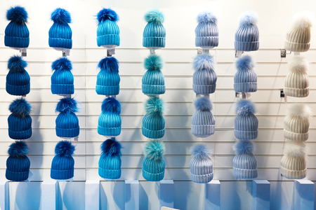 Winter hats of blue hues in the shop window