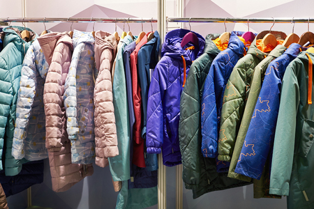 Winter jackets on a hanger in the store Фото со стока