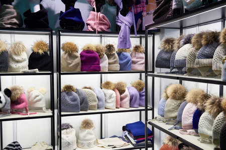 Winter colorful hats with fur pompom in the shop window