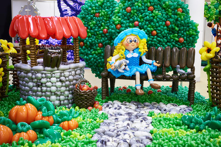 Girl on a bench in the garden. Craft from balloons Фото со стока