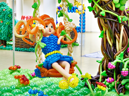 Girl on a swing in the garden. Craft from balloons