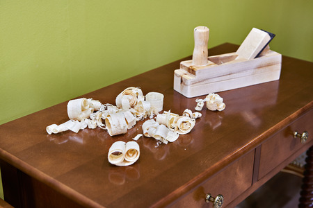 Joiner planer and wood shavings on finished furniture Stock Photo