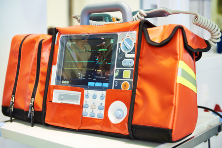 Modern portable biphasic defibrillator in orange bag