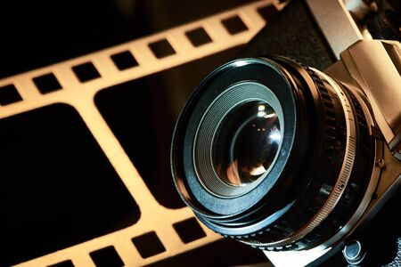 Lens SLR camera on the background of the perforation of film