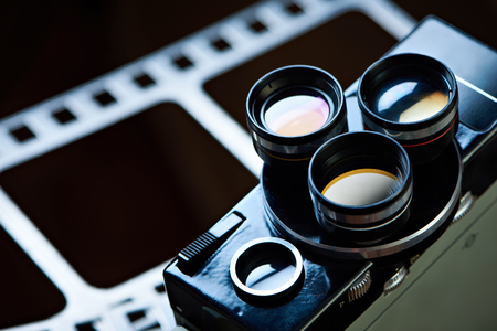 Old retro movie camera on the background of a perforation of film