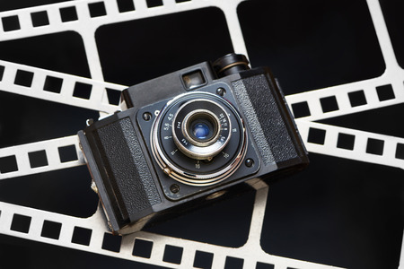 Old retro rangefinder camera on the background of the film perforation
