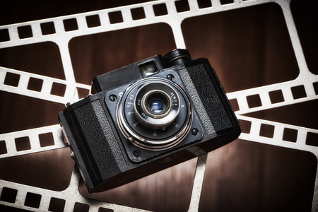 Old retro rangefinder camera on the background of film perforation