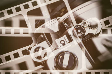 Retro SLR camera on the background of the perforation of film