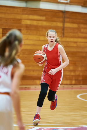 Girl basketball player with a ball in the game Фото со стока