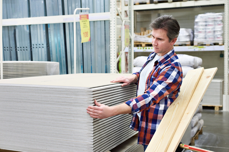 Man chooses and buys drywall in a construction supermarket