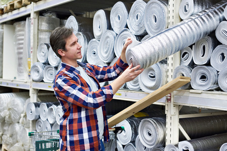 Man chooses and buys heat foil insulation in a construction supermarket