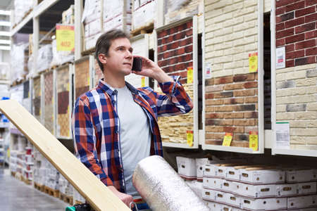 Man with smartphone chooses and buys goods in a construction supermarket
