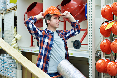 Man selects and buys a construction hard hat in a store