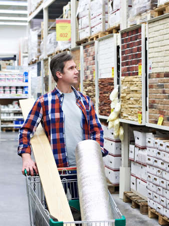 Man chooses and buys goods in a construction supermarket