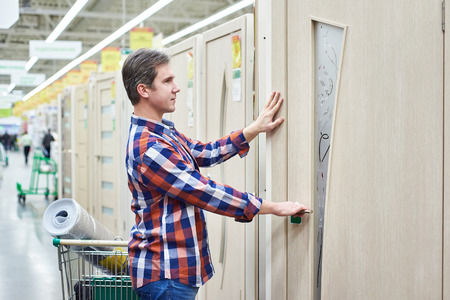 Man chooses a wooden door in a building store