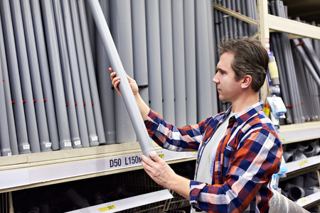 Man chooses plastic sewer pipes in a building store Фото со стока