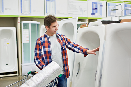 Man chooses a bath in a building store