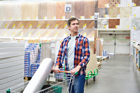 Man chooses and buys wooden board in a construction supermarket