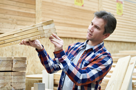 Man chooses and buys wooden boards in a construction supermarket