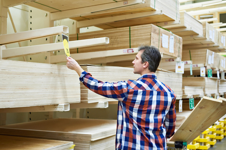 Man chooses and buys plywood in a construction supermarket Фото со стока