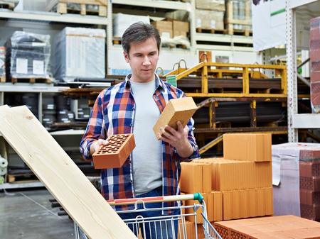 Man chooses and buys bricks in a construction supermarket Фото со стока