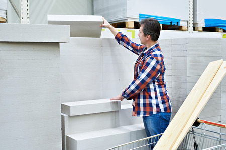 Man chooses and buys foam concrete bricks in a construction supermarket