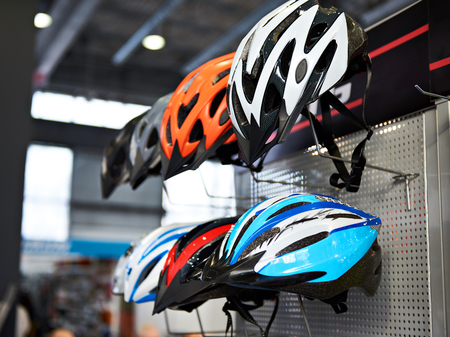Modern protective sports helmets for cyclists in the store