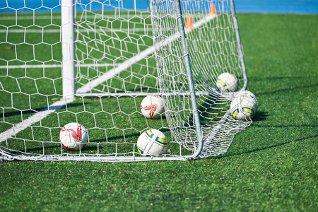 Balls in football goal on the field Фото со стока