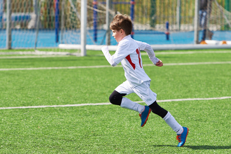 Running boy soccer player training on the football field