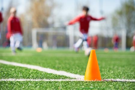 Orange cone for training football on the field Фото со стока