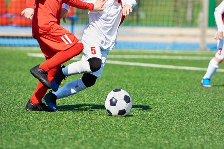 Child football players and ball on the football field Фото со стока